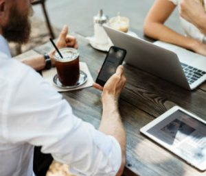 men looking at phone for social media while drinking a coffee
