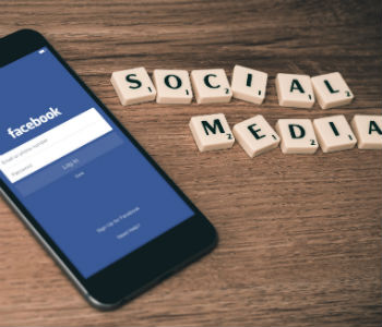 social media letters with facebook pulled up on phone
